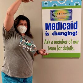 picture of melinda johnson pointing at medicaid sign